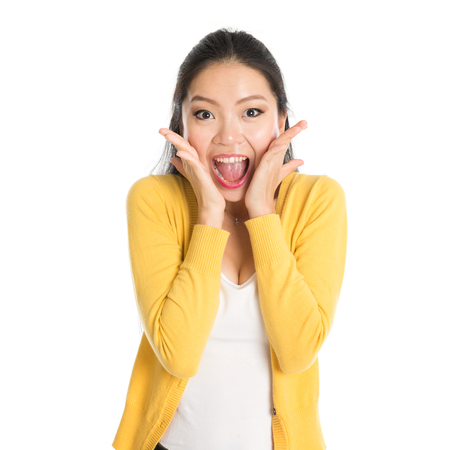 Shocked Asian woman mouth open wide, shouting and looking at camera, standing isolated on white background. Standard-Bild