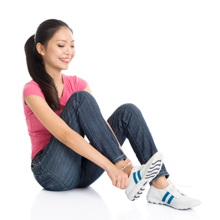 Portrait of young Asian woman in pink shirt and jeans wearing sneakers, full body seated isolated on white background.