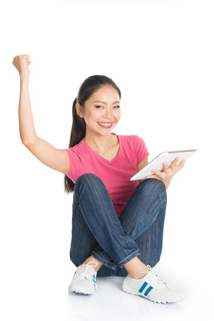 tab: Full body young Asian girl in pink shirt using digital tablet computer arm raised celebrating success, seated on floor, full length isolated on white background.