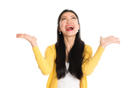 Surprised Asian woman mouth open wide, shouting and looking up, standing isolated on white background.