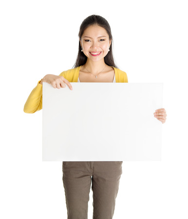 Portrait of casual Asian female hand holding blank white paper card and pointing on it, isolated on white background. Stock Photo