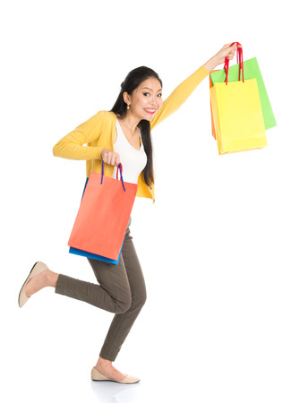woman shop: Happy young Asian woman shopper running, hands outstretched holding shopping bags and smiling, full length isolated standing on white background. Stock Photo