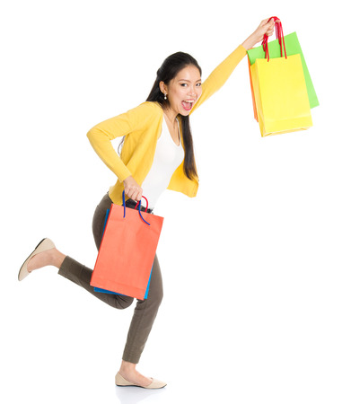 Happy young Asian female shopper running, hands outstretched holding shopping bags and smiling, full length isolated standing on white background.