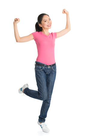 cheer full: Portrait of excited young Asian woman in pink shirt and jeans arms raised celebrating success, full body standing isolated on white background.