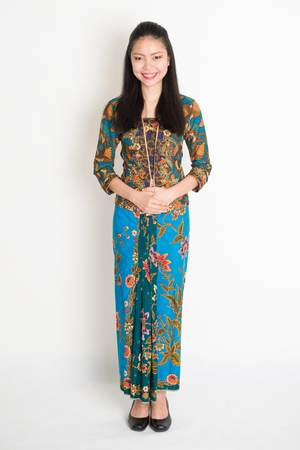 Portrait of young southeast Asian girl in traditional Malay batik kebaya dress smiling, full body standing on plain background. Stock Photo