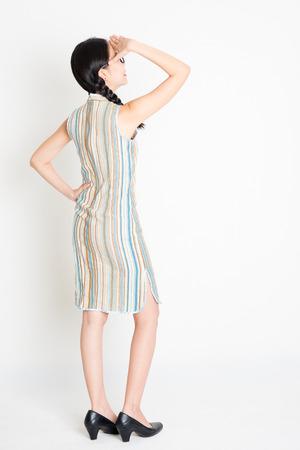 niñas chinas: Rear view of young Asian woman in traditional qipao dress hand shielding, full length standing on plain background. Foto de archivo