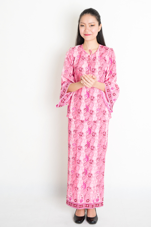 Portrait of young southeast Asian girl in traditional Malay batik dress greeting, standing on plain background. Stock Photo