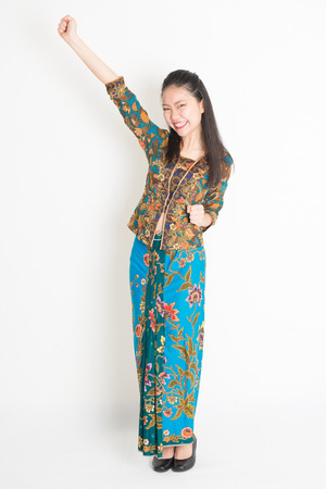 Portrait of young southeast Asian woman in traditional Malay batik kebaya dress arm raised celebrating success, full length standing on plain background. Stock Photo