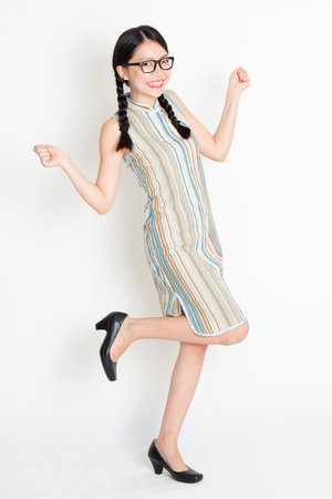 exaggerate: Portrait of excited young Asian girl in traditional qipao dress jumping around and hand holding something, full length standing on plain background.