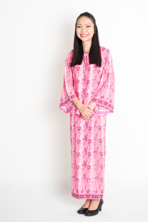 Portrait of young southeast Asian girl in traditional Malay batik dress smiling, standing on plain background.
