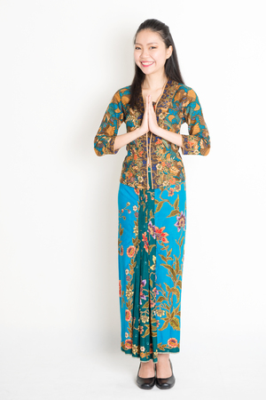 Portrait of young southeast Asian woman in traditional Malay batik kebaya dress greeting, full length standing on plain background. Stock Photo