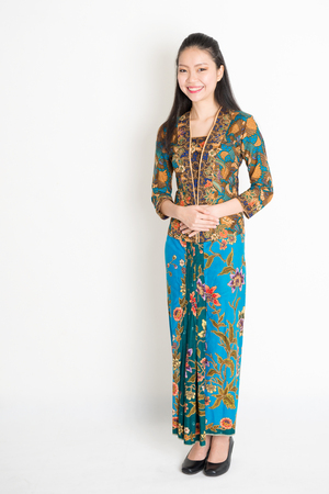 Portrait of young southeast Asian woman in traditional Malay batik kebaya dress smiling, full length standing on plain background. Stock Photo