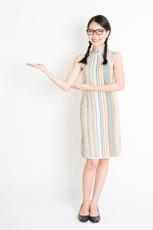 Portrait of young Asian girl in traditional qipao dress hands holding something, full length standing on plain background.
