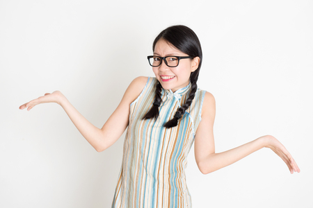 Portrait of young Asian girl in traditional qipao dress unsure and shrugging shoulder, standing on plain background. Stock Photo