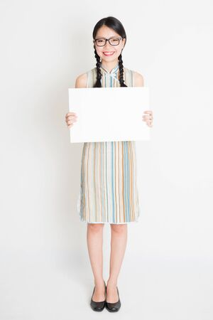 hold on: Portrait of young Asian woman in traditional qipao dress hand holding a white blank paper card, celebrating Chinese Lunar New Year or spring festival, full body standing on plain background.