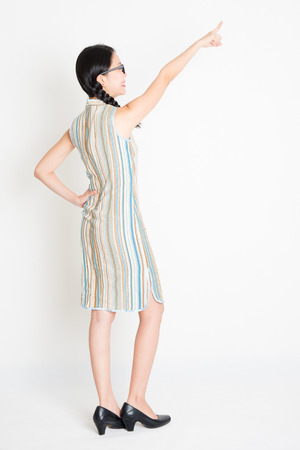 Rear view of young Asian girl in traditional qipao dress finger pointing away, full length standing on plain background. Stock Photo