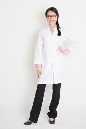 medical laboratory: Full length portrait of young Asian female scientist with lab coat standing on plain background. Stock Photo