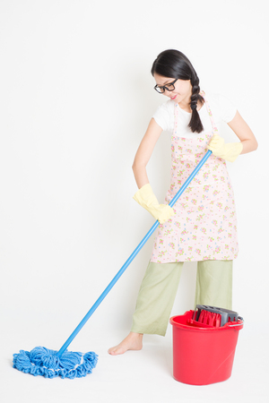 sirviente: Young Asian housewife mopping floor with water, home cleaning. Foto de archivo