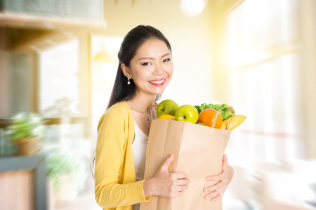 Young Asian woman hand holding shopping paper bag filled with fruits and vegetables in market store or cafe .  Stock Photo