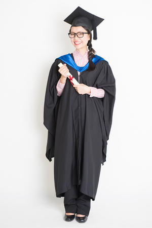 University student in graduation gown and cap holding diploma certificate. Full body portrait of east  Asian female model standing on plain background.
