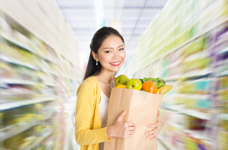asian produce: Young Asian woman hand holding shopping paper bag filled with fruits and vegetables in market or department store.  Stock Photo