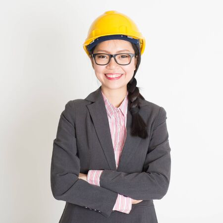 asian architect: Portrait of Asian female architect with hard hat smiling and looking at camera, standing on plain background. Stock Photo