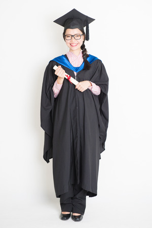 egresado: Happy university student in graduation gown and cap holding diploma certificate. Full body portrait of east  Asian female model standing on plain background.