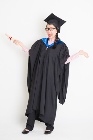 University student in graduation gown and cap holding diploma certificate laughing. Full body portrait of east  Asian female model standing on plain background.