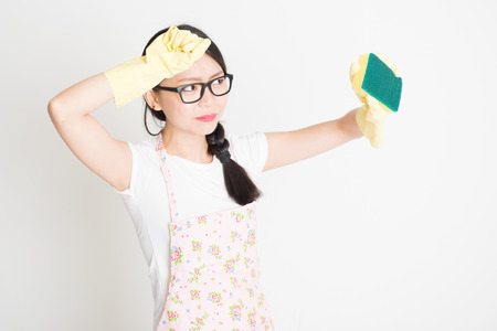 dirt: Young Asian housewife with sponge scrubbing dirt.