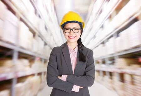 warehouse: Young Asian female store manager with hard hat arms crossed standing in storehouse. Shelves with goods at background.