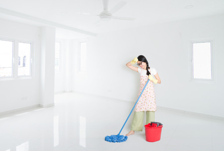 Young Asian woman mopping floor with water, cleaning house.