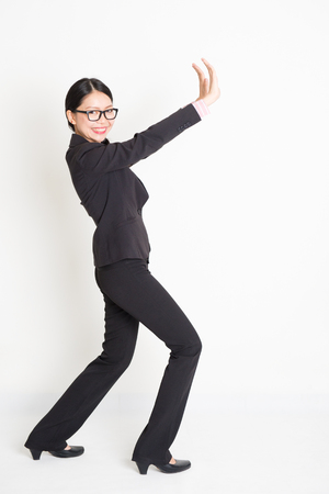 Full body portrait of young Asian businesswoman in formalwear hands pushing on something and smiling, standing on plain background.