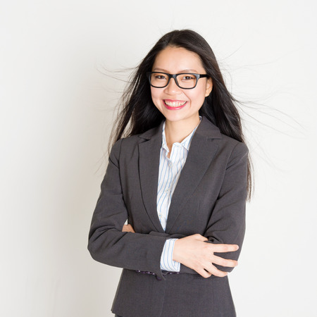 Portrait of young Asian businesswoman in formalwear smiling and looking at camera, standing on plain background. 스톡 콘텐츠