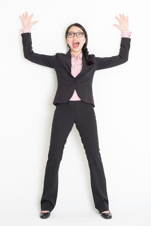 Full length front view of shocked young Asian businesswoman in formalwear bang and leaning on wall, standing on plain background. Stock Photo