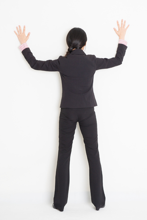 banging: Full body back view of young Asian businesswoman in formalwear banging on wall, standing on plain background. Stock Photo