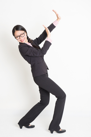Full body portrait of young Asian businesswoman in formalwear hands defending on something, standing on plain background.