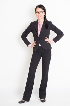 Full body portrait of young Asian businesswoman in formalwear hands on waist and smiling, standing on plain background.