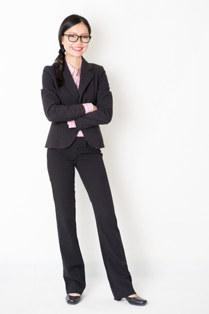 Full body portrait of young Asian businesswoman in formalwear arms folded and smiling, standing on plain background. Stock Photo