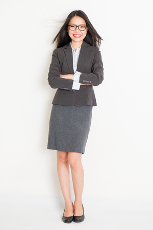 confident business woman: Portrait of Asian female business woman in formalwear smiling, full body standing on plain background.