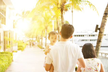 outdoor outside: Rear view of young family enjoying outdoor activity together, walking in beautiful sunset during holiday vacation, outside the resort.
