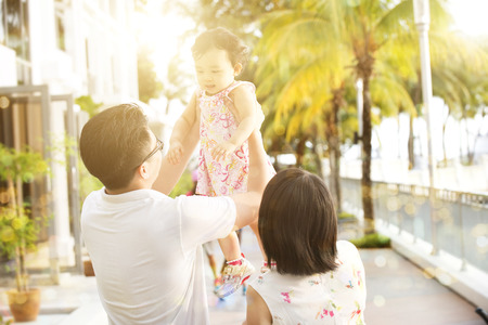 family playing: Rear view of Asian family enjoying outdoor activity together, playing with kid in beautiful sunset during holiday vacation, outside the resort.