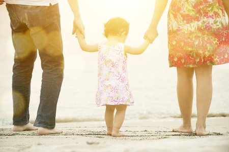 Happy Asian family outdoor activity, holding hands together walking on sand seaside in sunset during vacations.