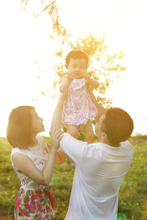 Portrait of lovely family enjoying outdoor activity together, walking on garden park in beautiful sunset during holiday vacations. photo
