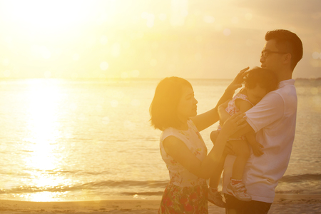 Silhouette of Asian family outdoor portrait, enjoying holiday together on seaside in beautiful sunset during vacations. photo