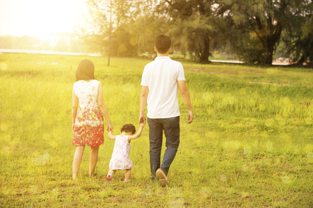 Rear view of Asian family enjoying outdoor activity together, walking on garden lawn in beautiful sunset during holiday vacations. photo