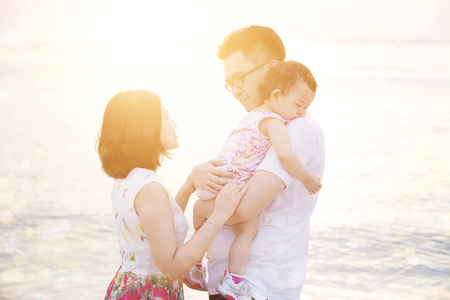 Happy Asian family outdoor portrait, enjoying holiday together on coastline in beautiful sunset during vacations. photo