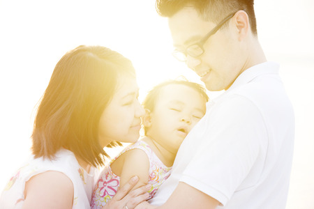 Lovely Asian family outdoor portrait, enjoying holiday together on seaside in beautiful sunset during vacations. photo