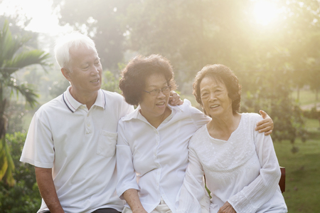 Portrait of healthy Asian seniors group having good time at outdoor nature park, in morning beautiful sunlight at background.