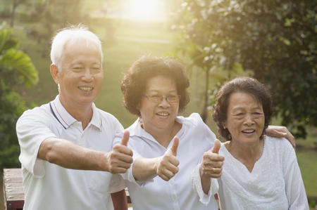 Group of cheerful Asian seniors retiree giving thumbs up at outdoor nature park, in morning beautiful sunlight at background.