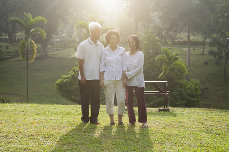 Group portrait of healthy and happy Asian seniors retiree walking at outdoor nature park, in morning beautiful sunlight at background. photo
